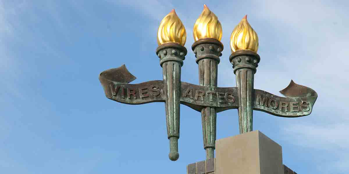 Photo of torches above the Heritage Fountain reading Vires • Artes • Mores